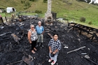 Tane Croft-Ritete, front, with his aunty Astor Toia, left and grandfather Hamlin James Croft at the scene of the fire which destroyed Tane's future home in Motatau the night he and his mother Lottie were due to move in. Photo / John Stone