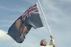 Peter Jackson waves a new New Zealand flag with a picture of Stephen Joyce being hit by a dildo at Waitangi. Photo / Supplied