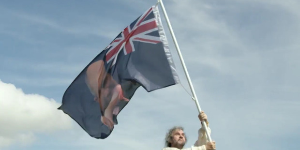Peter Jackson waves a new New Zealand flag with a picture of Stephen Joyce being hit by a dildo at Waitangi. Photo / Last Week Tonight