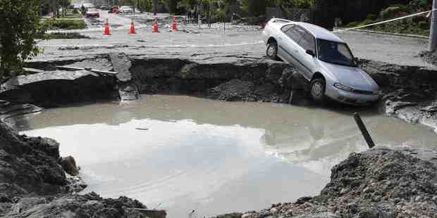 An abandoned car rests in a massive hole in Mackenzie Ave in Christchurch after the 2011 6.3 earthquake. Photo / Greg Bowker