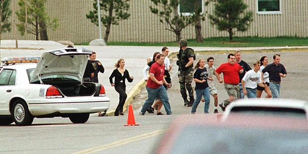 Students run from Columbine High School run for cover during the massacre. Photo / Getty