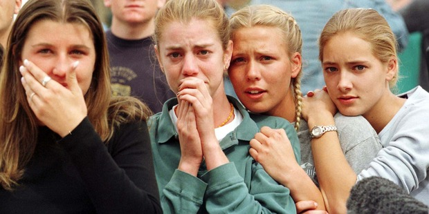 Students from Columbine High School watch as the last of their fellow students are evacuated. Photo / Getty