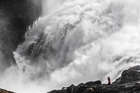 A woman (dressed as  Huldra) sings in front of the Kjosfossen waterfall in Norway. Photo / Markus Trienke