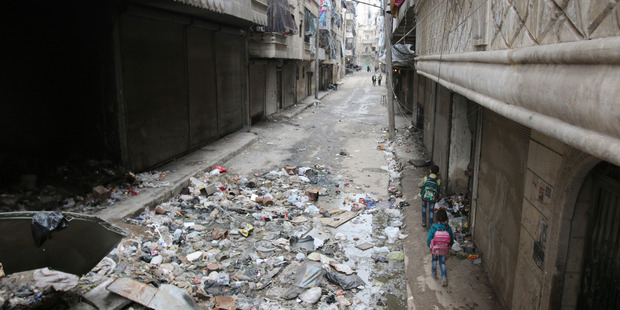 Children walk down a damaged street in Aleppo, Syria. Photo / AP