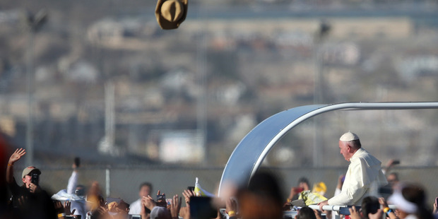 A hat flies in the air as Pope Francis arrives for a massive open-air Mass in a park just a few meters from the U.S. border in Ciudad Juarez, Mexico. Photo / AP