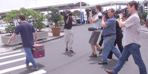 Colin's is greeted by the New Zealand media on arrival back at Auckland International Airport. Photo / NZ Herald