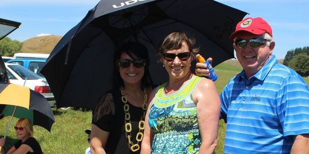Sari Lamborn (under umbrella) and Sharron and Lloyd Passey picnicking in the carpark before the game. The Lamborns were at the game to see son Tony run on for the Hurricanes. Photo / Christine McKay