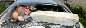 Andy Sinclair with a concrete block vandals used to smash the back window of his car.