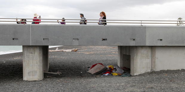 Tourists take photos of scenery from the Viewing Platform on Marine Parade, Napier, just above a pile of sleeping gear, clothing and shoes which belong to a homeless person. Photo / Duncan Brown