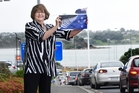 Councillor Gail McIntosh, who supports change, holds the alternative flag. Photo / George Novak
