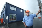 Richard Ive in front of the shop which was gutted by fire more than a year ago. Photo / John Borren