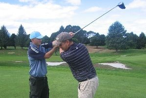 NZPGA class A professional coach Nicholas Davey (right) demonstrates the right position.