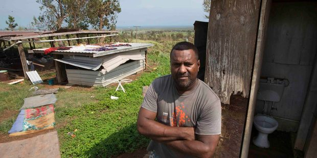 Seru Pepeley, in the background is the chicken shed, where his mother-in-law has been forced to live after her house was destroyed. Photo / Brett Phibbs