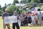 Paul Shaw (front left) presented a cheque for $25,000 to Barry Vincent from the Bay Trust Rescue Helicopter on Sunday. Photo / Stephen Parker