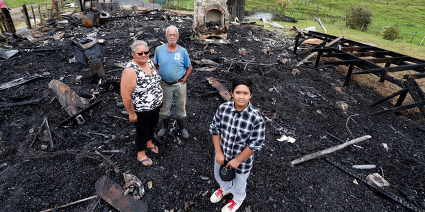 Tane Croft-Ritete, front, with his aunty Astor Toia and grandfather Hamlin James Croft at the scene of the fire which destroyed Tane's future home in Motatau. PHOTO/JOHN STONE