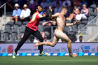 A streaker runs across the field chased by a security guard at Hagley Oval in Christchurch. Photo / Getty Images