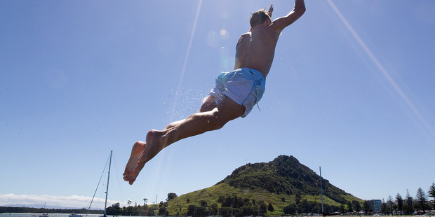 William Clague takes a big leap into the cool waters of Pilot Bay in Tauranga Harbour today. Photo / Alan Gibson
