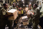 Aid supplies are unloaded by Fijian soldiers from an RNZAF C-130 Hercules in Suva, Fiji. Photo: Supplied
