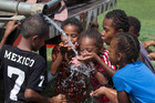 Children drink water from a water tanker a evacuation centre at Lovu Seaside School, after cyclone Winston hit Fiji. Photo / Brett Phibbs