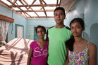 Premila and Salesh Kumar and their daughter, Priyashna, inside their wrecked home, also shown below. Photo / Brett Phibbs