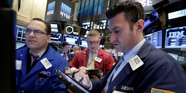 Specialist Anthony Matesic, left, works at his post on the floor of the New York Stock Exchange with traders Ryan Falvey, center, and Glenn Kessler. Photo / AP