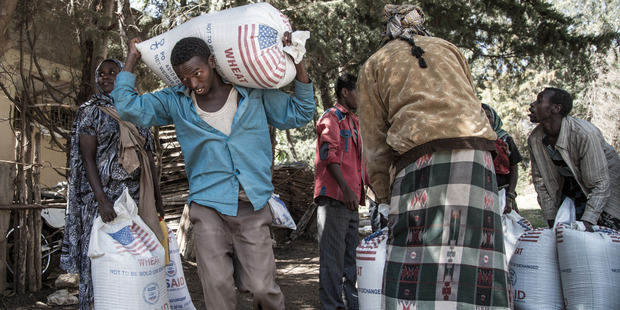 A man carries his portion of rationing of wheat for his family, each day around 900 households are provided with wheat, oil and split peas for a month. Photo / Aida Muluneh, Washington Post