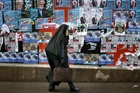 An Iranian woman walks past electoral posters of parliamentary election candidates in Tehran but her vote may not count for much. Picture / AP