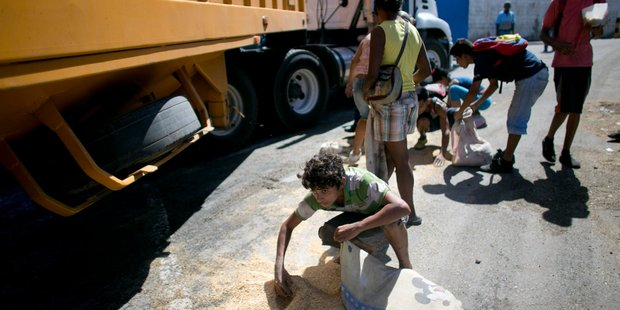 A youth uses his pillow as a bag to collect rice from the pavement that shook loose from a food cargo truck in Puerto Cabello, Venezuela. Photo / AP