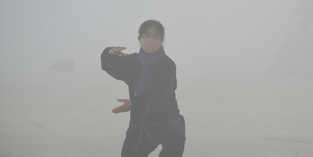 A woman wearing a protection mask practices tai-chi at a park blanketed by severe smog in Fuyang in central China's Anhui province. Photo / AP
