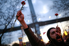 People holding carnations chant slogans at the scene of the nightclub New Year's attack, in Istanbul. Photo / AP