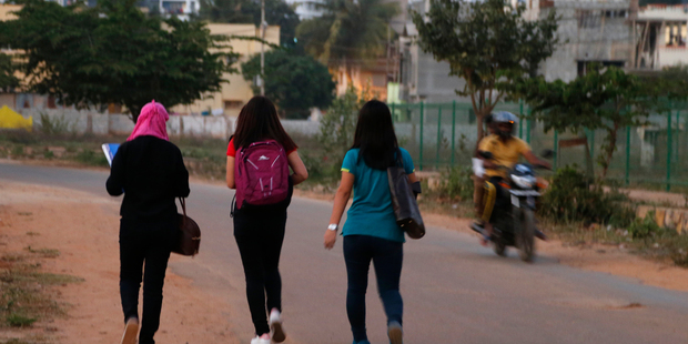 A motorist rides past young Indian girls in Bangalore, India. Police detained at least six suspects, days after outrage erupted in India over several women being groped and molested. Photo / AP