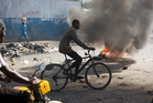A man cycles past burning tires set by protesters against the final election results in Port-au-Prince, Haiti. Photo / AP