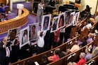 Photos of victims of the shooting at Emanuel AME Church in Charleston, South Carolina, are held during a vigil in June 2015.