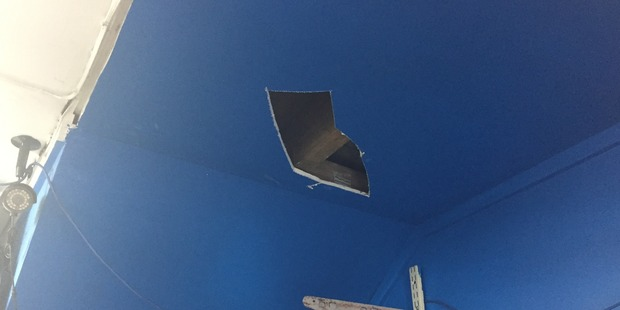The robber fired a bullet into the ceiling of the store before taking off with cash from the till.