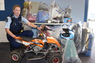 CRIME BUST: Constable Erin Collins with bags of stolen items as well as a mini quad bike being held at Kapiti police station.