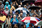 Fans take shelter as rain stops play between Jade Lewis and Venus Williams. Photo / Dean Purcell