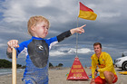 Mount Maunganui Surf Lifesaving Club Patrol Captain Sam Roy talking to two-and-half-year-old local Max McCormick about swimming between the flags. Photo/George Novak.
