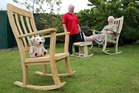 Sue Painting (left), Ngaire Podjursky and Teddy get to test drive the rocking chairs made by Peter Painting. PHOTO/STUART MUNRO