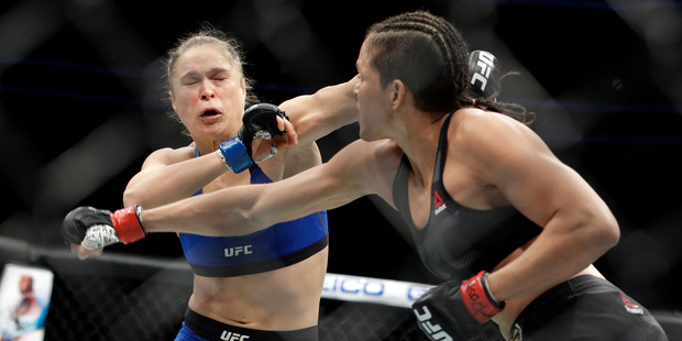 Amanda Nunes throws a punch at Ronda Rousey during their bout at UFC 207. Photo/AP Photos