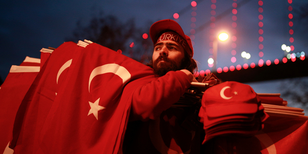 People carrying Turkish flags gather at the scene of the nightclub New Year's Day attack, in Istanbul. Photo / AP