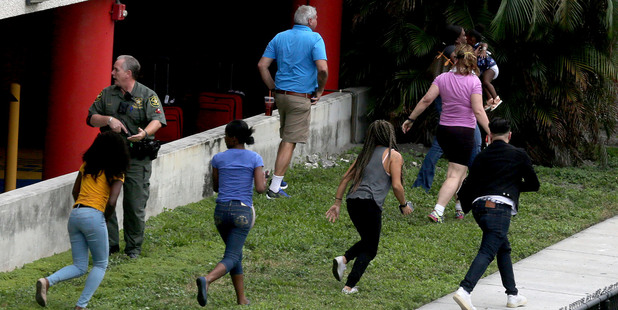 People flee the area outside the Fort Lauderdale-Hollywood International airport after a shooting took place. Photo / AP