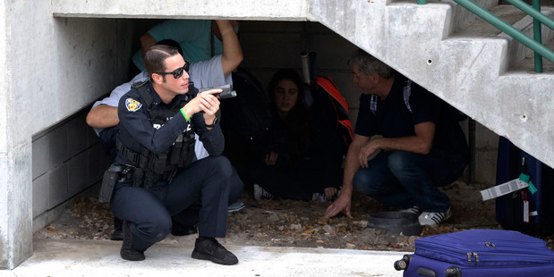 Law enforcement personnel shield civilians outside a garage area at Fort Lauderdale Hollywood International Airport. Photo / AP