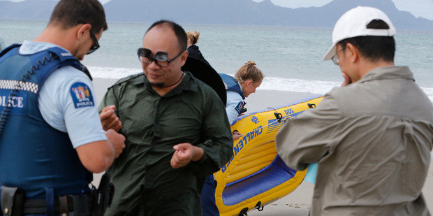 The Auckland man (centre) who was rescued when his small inflatable craft was blown 1.5km in strong westerly winds off Uretiti Beach during a crab fishing expedition. Photo / John Stone