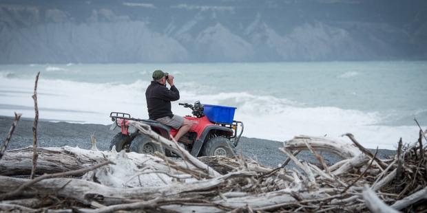 Searchers scan the coastline at Onoke spit, Lake Ferry. Photo / Wairarapa Times-Age