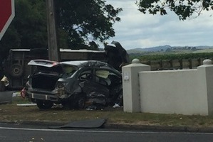 A silver sedan crashed through a thick concrete wall after swiping a campervan which has been left on its side in the background. Photo / Supplied
