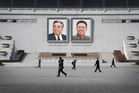 People walk past portraits of the late North Korean leaders Kim Il Sung and Kim Jong Il at Kim Il Sung Square in Pyongyang, North Korea. Photo / AP