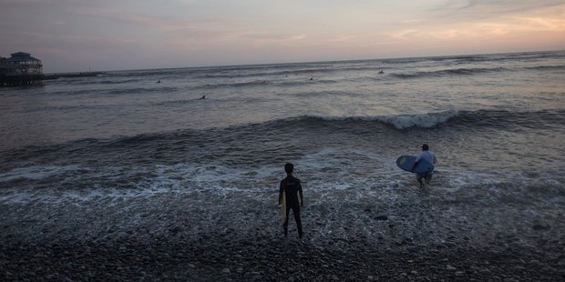 Surfers enter the Pacific Ocean as the sun sets, on Waikiki Beach in Lima, Peru. Photo / AP