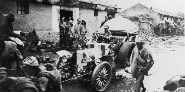 A participant in the Paris to Peking rally in 1907 is pulled along a muddy street. Photo / Getty Images