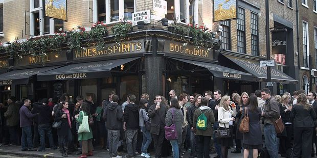 Drinkers spill out onto the street outside The Dog and Duck pub in Soho, London. Photo / Getty Images