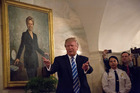 President Donald Trump walks in a corridor of the White House to greet visitors, while a portrait of Hillary Clinton hangs on the wall. Photo / Getty